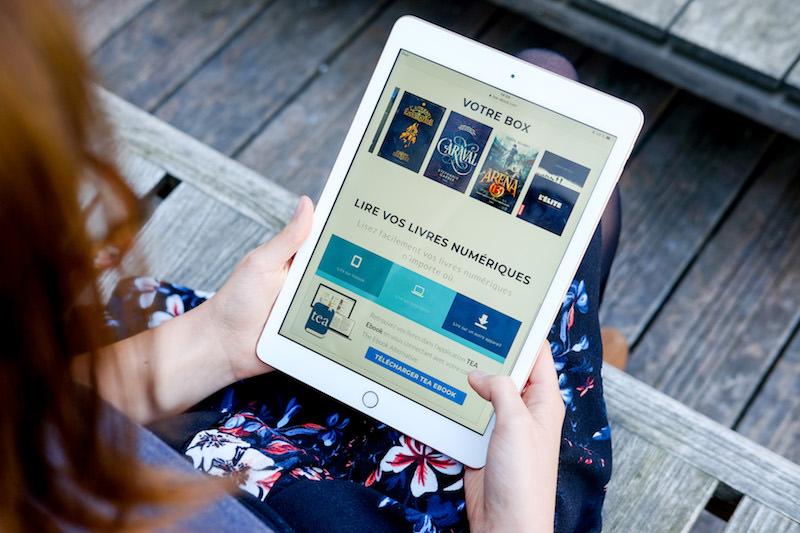 Une jeune femme tient une tablette affichant le contenu de sa Box Ebook